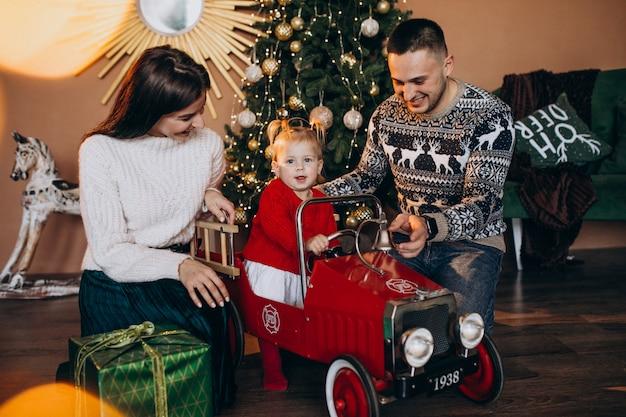 Famille avec petite fille avec un cadeau de noël par sapin de noël Photo gratuit
