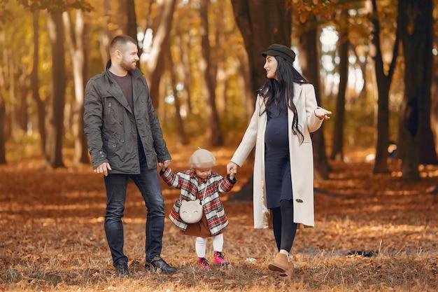 Famille avec petite fille dans un parc en automne Photo gratuit