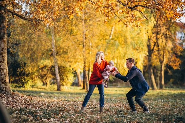 Famille avec petite fille marchant dans un parc en automne Photo gratuit