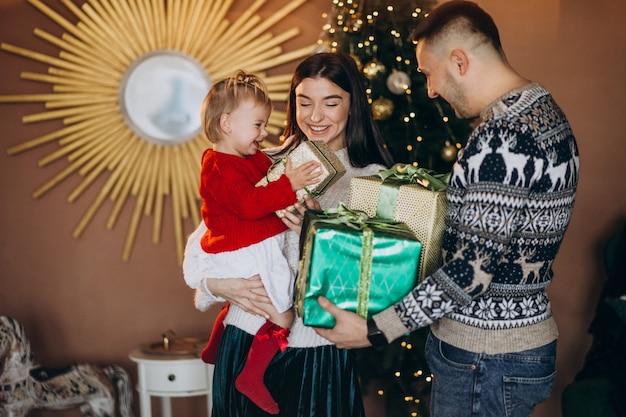 Famille avec petite fille près de boîte de cadeau de déballage d'arbre de noël Photo gratuit