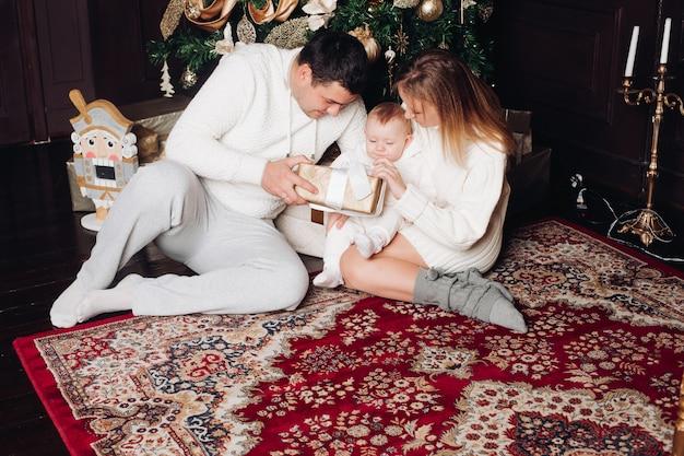 Famille posant dans le salon décoré. adorable femme, homme et bébé vêtus de confortables vêtements tricotés blancs. Photo Premium