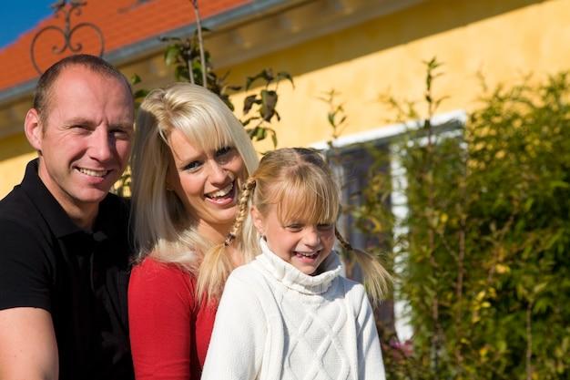 Famille posant devant une maison Photo Premium