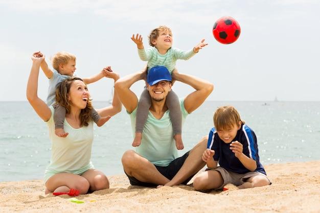 Famille positive de cinq jouant à la plage de la mer Photo gratuit
