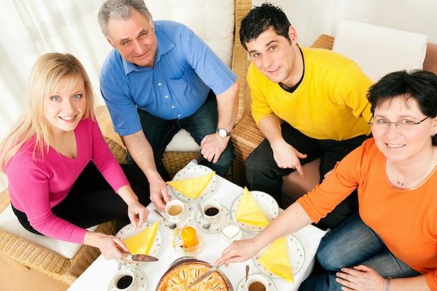 Famille prenant un café et un gâteau ensemble Photo Premium
