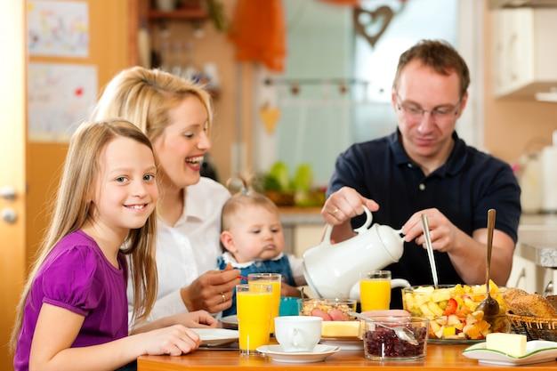 Famille prenant son petit déjeuner dans la cuisine de leur maison Photo Premium