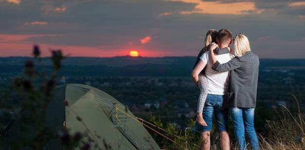 Famille près de la tente de camp sur la colline Photo Premium