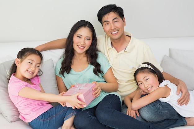 Famille présentant une mère heureuse avec une boîte-cadeau dans le salon Photo Premium