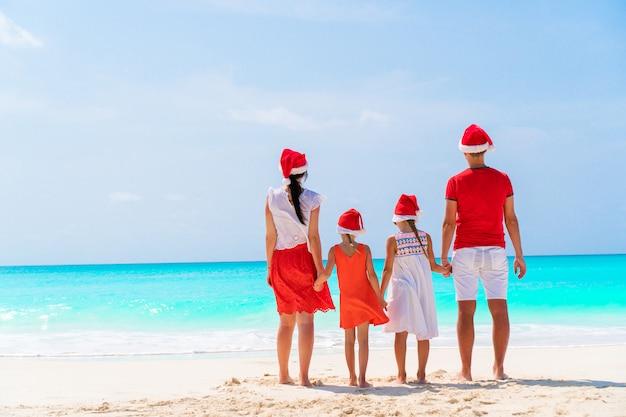 Famille, quatre, dans, rouges, santa, chapeaux, sur, a, plage tropicale, célébrer noël Photo Premium