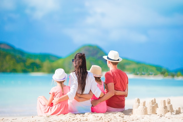Famille de quatre personnes faisant un château de sable sur une plage blanche tropicale Photo Premium