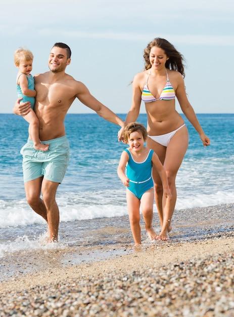Famille de quatre personnes à la plage Photo gratuit