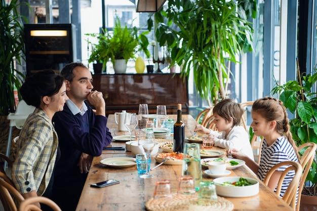 Une Famille De Quatre Personnes En Train De Dîner Dans Un Café Photo Premium