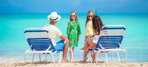Famille de quatre personnes en vacances à la plage Photo Premium