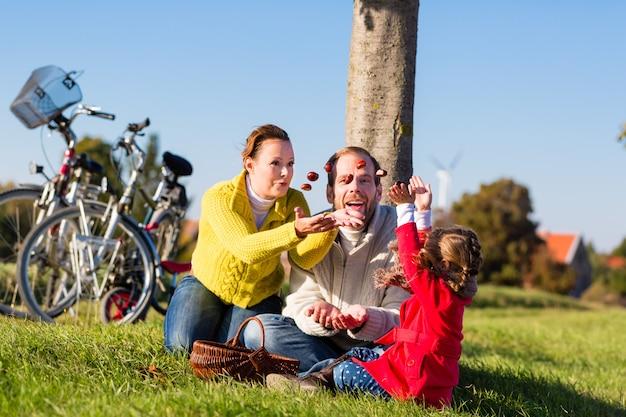 Famille ramassant des châtaignes lors d'un voyage à vélo Photo Premium