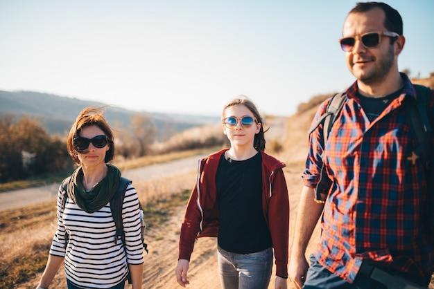 Famille de randonnée ensemble sur une route sale de montagne Photo Premium