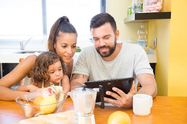Famille regardant l'écran de la tablette numérique pendant le petit déjeuner Photo gratuit