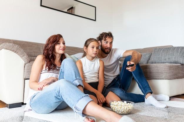 Famille regardant la télé ensemble Photo gratuit