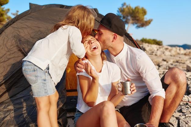 Famille Reposant Sur La Côte Rocheuse, Fille Tendant La Main Pour Embrasser Sa Mère. Photo Premium