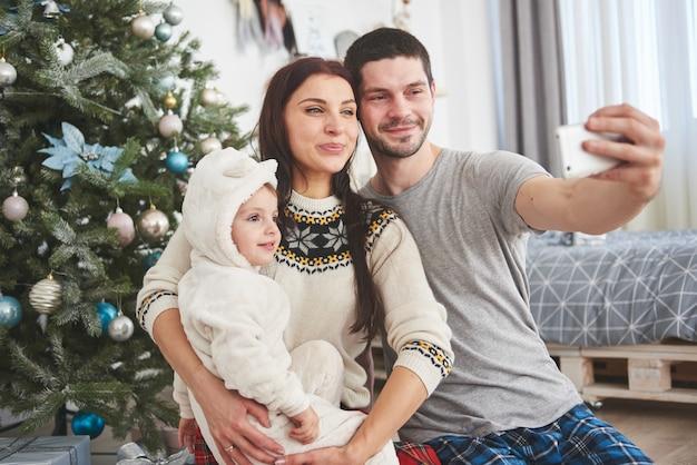 Famille Réunie Autour D'un Arbre De Noël, à L'aide D'une Tablette Photo Premium