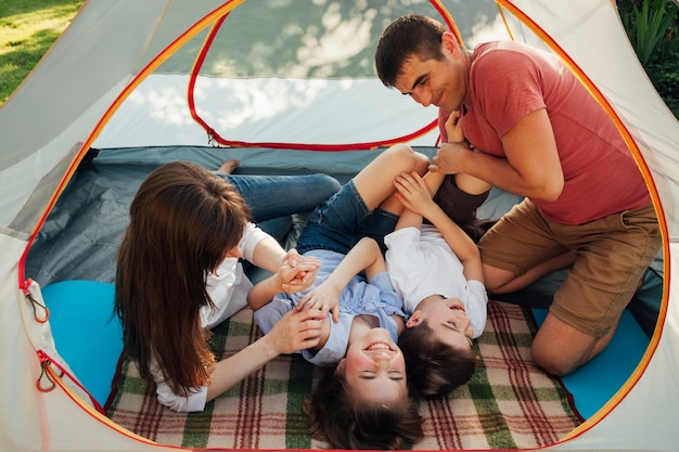 Famille s'amuser sous la tente en vacances de camping Photo gratuit