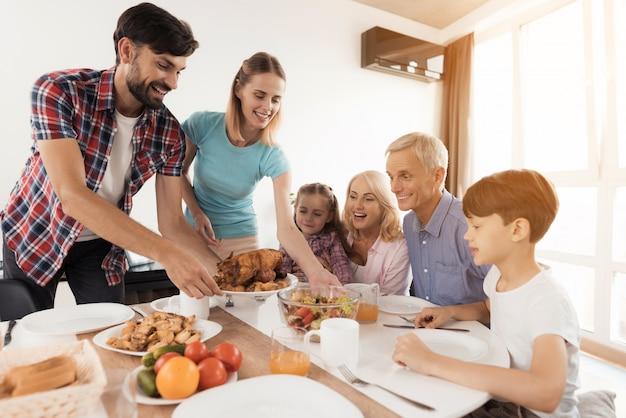 La famille s'assoit pour le dîner de thanksgiving. Photo Premium