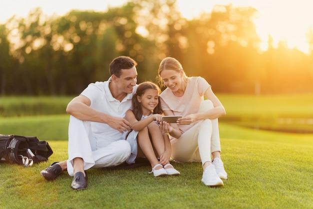 La famille se repose après les photos de montres de golf. Photo Premium