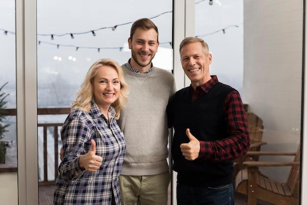 Famille Smiley Posant Avec Son Fils Et Les Pouces Vers Le Haut Photo gratuit