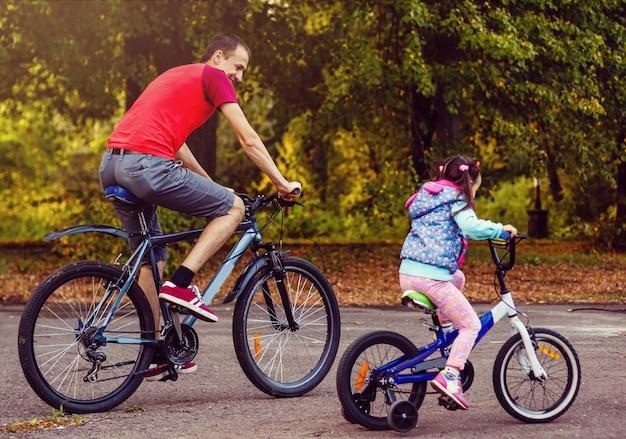 Famille sport père et fille à vélo dans la forêt verte Photo Premium