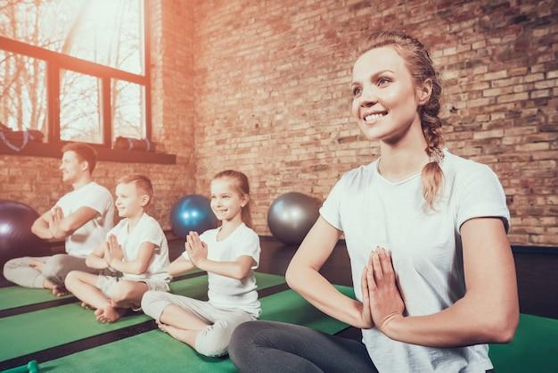Famille sportive avoir une formation de yoga au club de fitness. Photo Premium