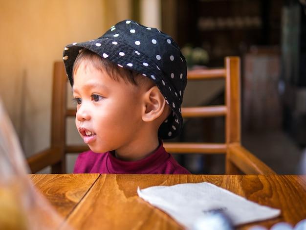 Famille très amusante de mère asiatique nourrissant une boulangerie avec sa jolie fille au café. Photo Premium