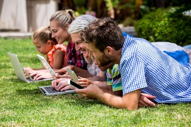 Famille Utilisant Des Technologies Tout En Se Relaxant Au Parc Photo Premium