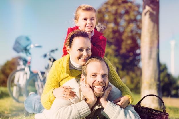 Famille à vélo dans un parc en automne Photo Premium