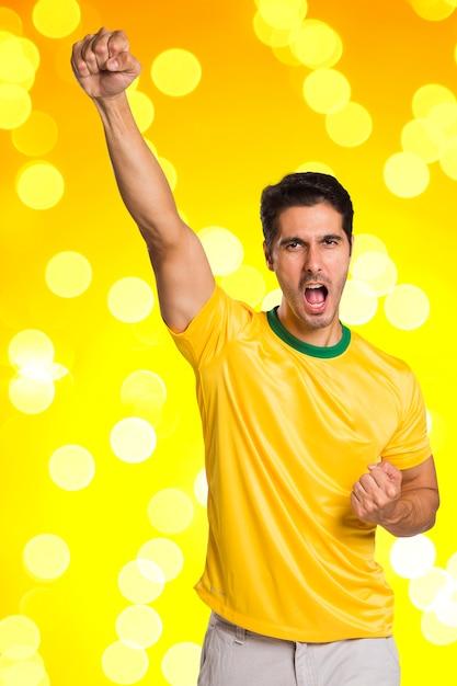 Un Fan Brésilien Célèbre Sur L'espace Jaune Photo Premium
