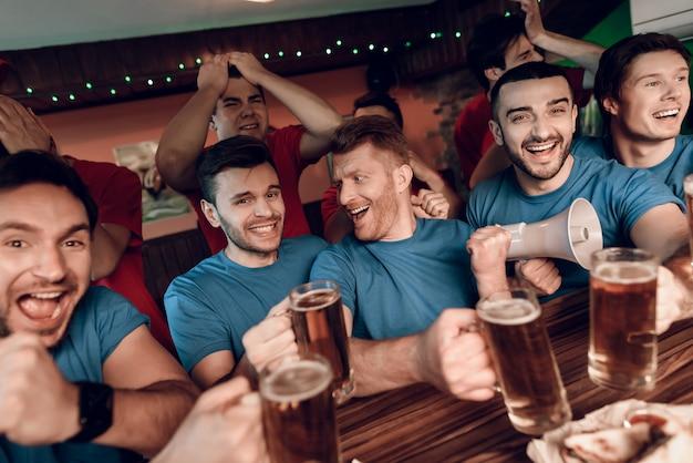 Les fans de l'équipe bleue célèbrent et applaudissent au bar. Photo Premium