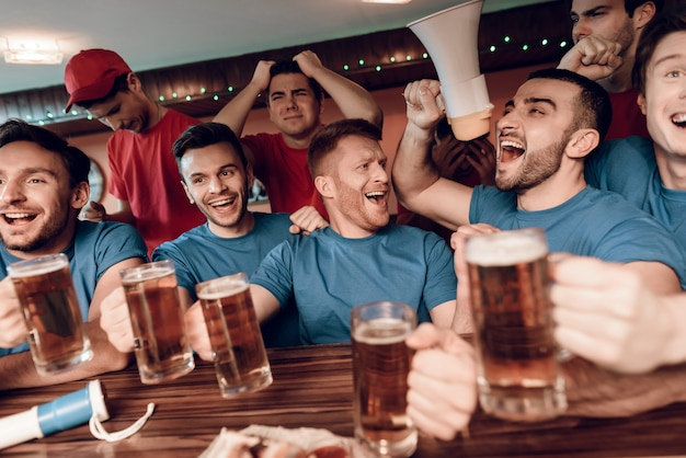 Les fans de l'équipe bleue célèbrent et encouragent au bar Photo Premium