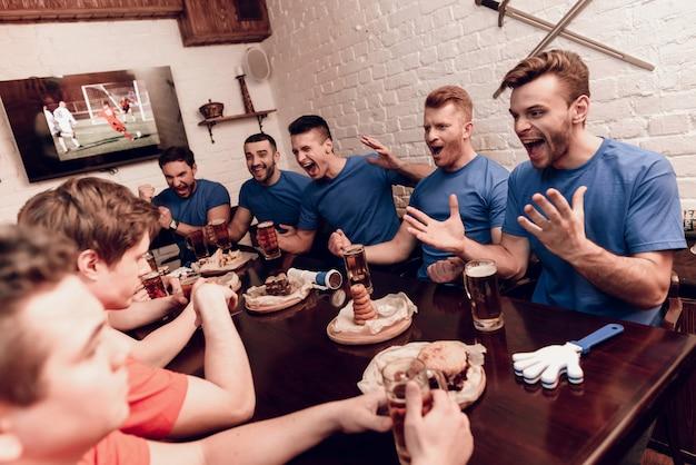 Les fans de l'équipe rouge sont tristes alors que les fans bleus sont au bar Photo Premium