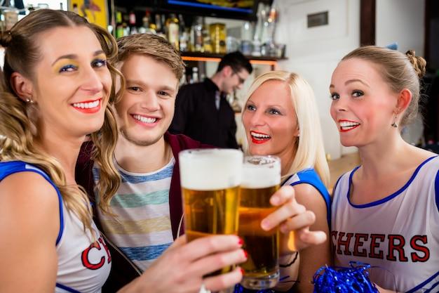 Fans d'une équipe sportive en train de regarder un match au bar Photo Premium