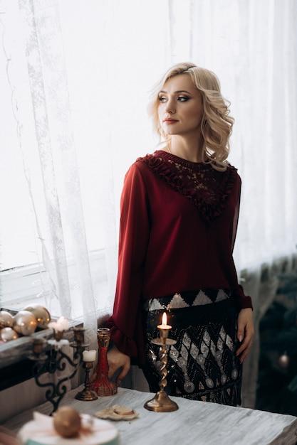 Fantaisie femme blonde vêtue de vêtements rouges se trouve dans une chambre avec un décor de noël Photo gratuit