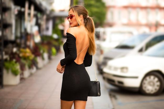 Fantaisie Jeune Femme Marchant Dans Une Ville Dans La Journée Dans Une Robe Noire Avec Dos Sexy Ouvert Et Manches Longues. Bourse à L'épaule. Cheveux Blonds Dans Une Coiffure. Maquillage Et Lunettes Modernes. Peau Douce Et Tendre Photo gratuit