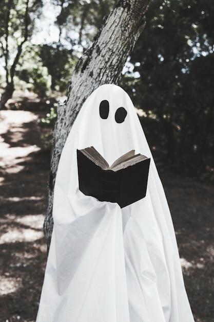 Fantôme appuyé sur un arbre et livre de lecture Photo gratuit