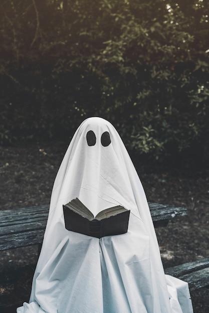 Fantôme assis sur un banc et livre de lecture Photo gratuit