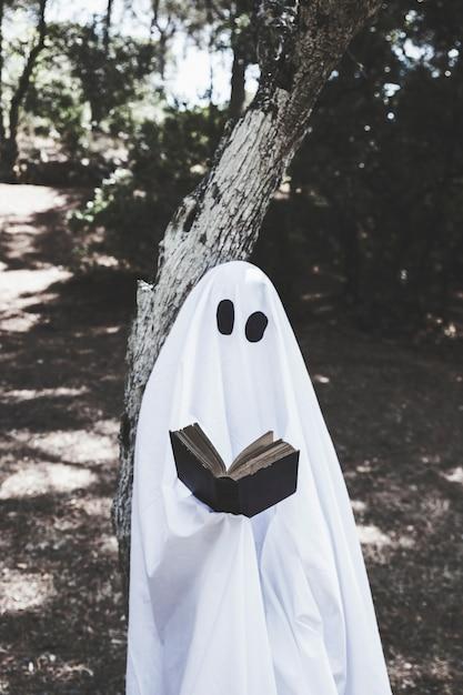 Fantôme debout à l'arbre et livre de lecture Photo gratuit