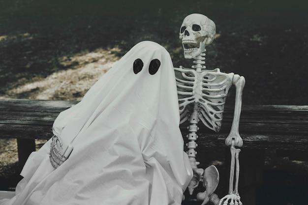 Fantôme et squelette étreignant sur un banc Photo gratuit