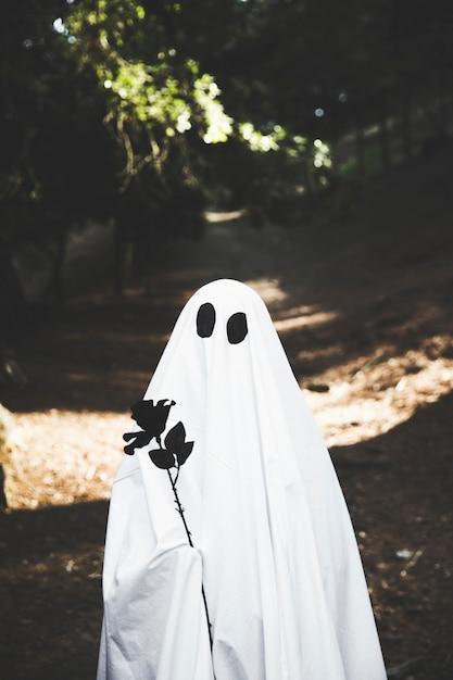Fantôme tenant une rose noire dans un parc Photo gratuit