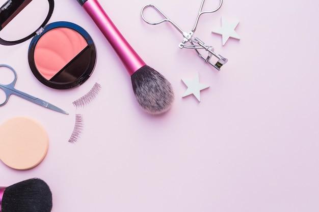 Fard à joues rose; éponge; les ciseaux; les cils; recourbe-cils et pinceau de maquillage sur fond rose Photo gratuit