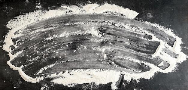Farine de blé blanche dispersée sur un tableau noir Photo Premium