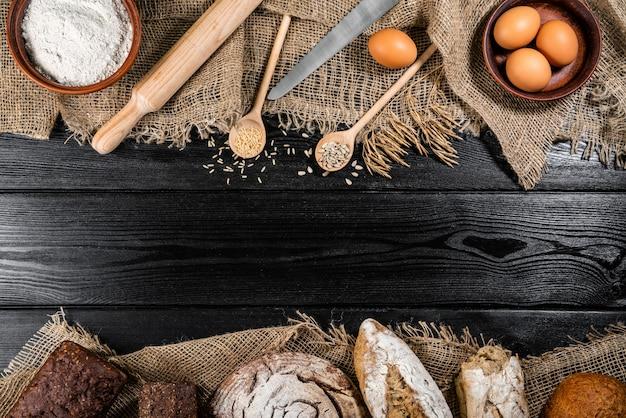 Farine Dans Un Bol En Bois Sur Une Table En Bois Sombre Avec Des épillets De Blé, Des œufs Photo Premium