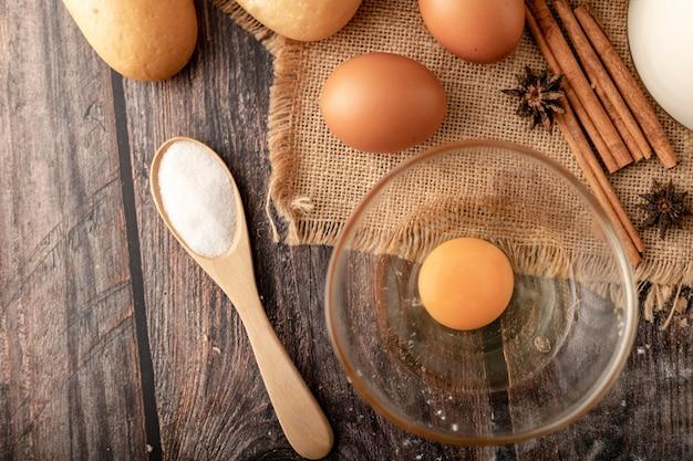 Farine dans une cuillère en bois et des œufs dans un verre sur le sac Photo Premium