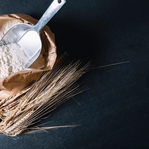 Farine avec pelle dans un sac en papier et oreille de blé sur fond texturé noir Photo gratuit