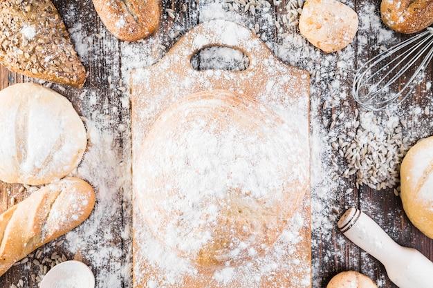 Farine sur la planche à découper et variété de pains sur la table Photo gratuit