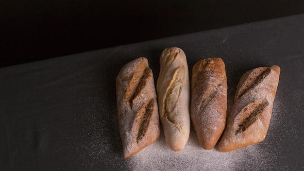 Farine saupoudrée sur du pain cuit au four sur fond noir Photo gratuit